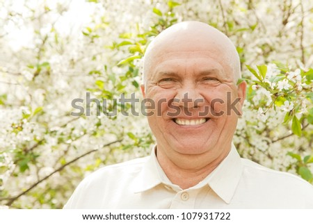 Portrait of gray-haired middle-aged man in the garden