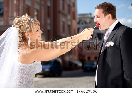 Portrait of greedy bride taking lollipop from groom while he was eating it - stock photo