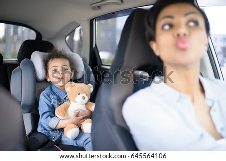 portrait of grimace mother and daughter driving in car together