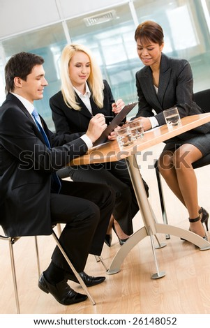 Portrait of group of business people looking at new plan and discussing it - stock photo
