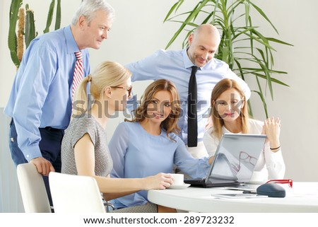 Portrait of group of businesswomen and businessmen sitting around conference table.  Business people working with laptop and digital tablet while consulting and working on business presentation. - stock photo