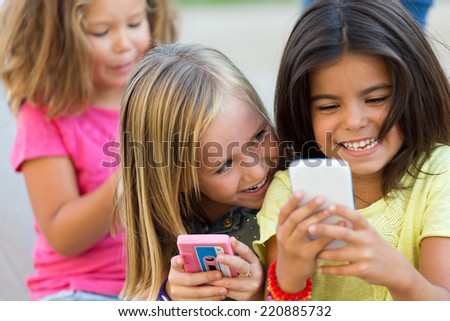 Portrait of group of childrens chatting with smart phones in the park. - stock photo