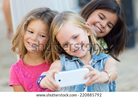 Portrait of group of childrens taking a selfie in the park. - stock photo