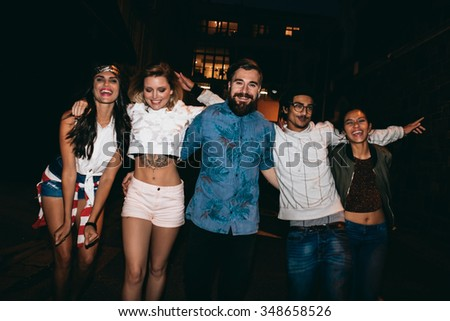 Portrait of group of friends having party together, outdoors. Multiracial young people hanging out in evening. - stock photo