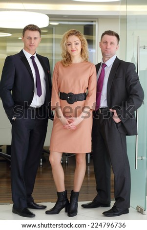 Portrait of group of happy business people: two men and woman at entrance to conference hall - stock photo
