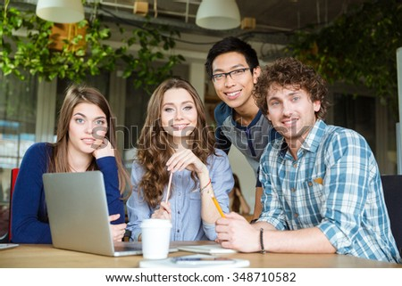 Portrait of group of happy cheerful attractive young students sitting at the table with laptop  - stock photo