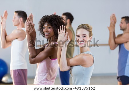 Portrait of group of people exercising in fitness studio