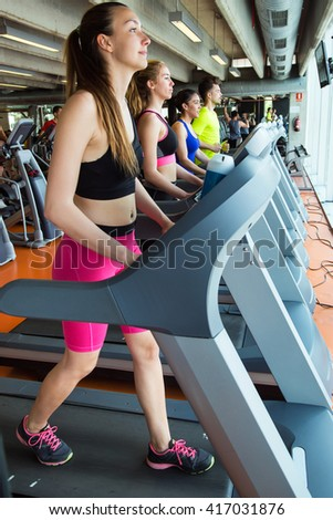 Portrait of group of people exercising their legs doing cardio training in gym. - stock photo