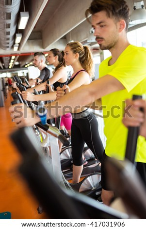 Portrait of group of people exercising their legs doing cardio training in gym.