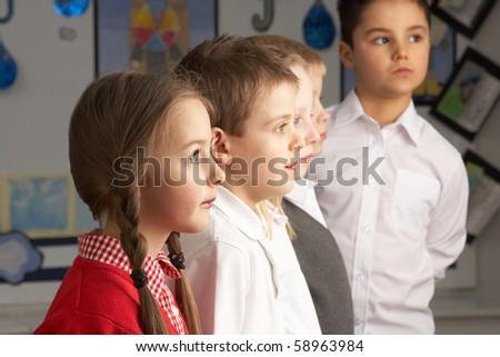Portrait Of Group Of Primary Schoolchildren Standing In Classroom - stock photo