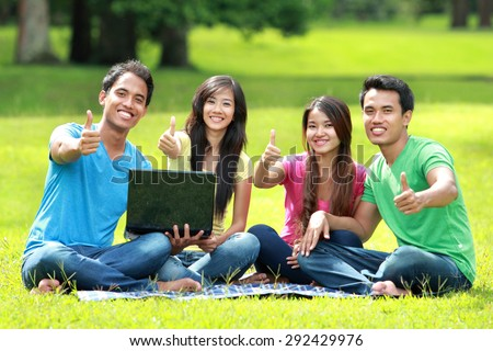 portrait of Group of students studying in the park using laptop computer. showing thumb up and looking at camera