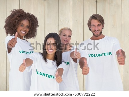 Portrait of group of volunteers showing thumbs up against wooden background