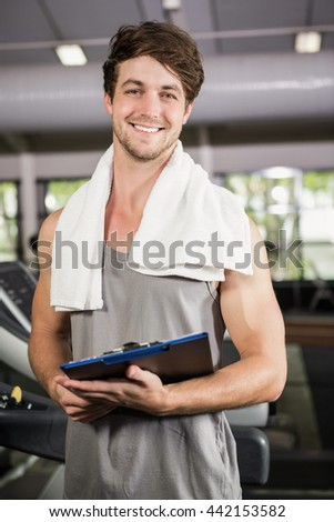 Portrait of gym instructor holding clipboard at gym