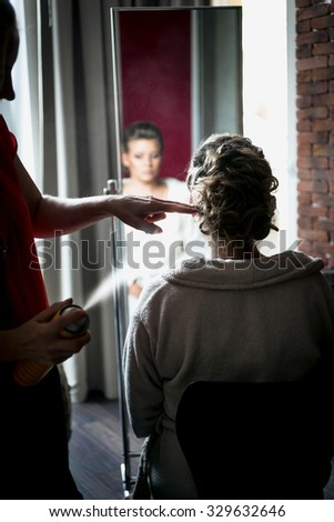 Portrait of hairstylist using hairspray on blonde bride's hair - stock photo