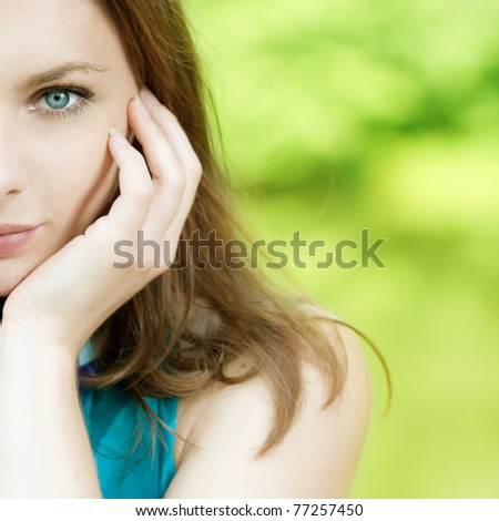 portrait of half face beautiful young woman on green background - stock photo