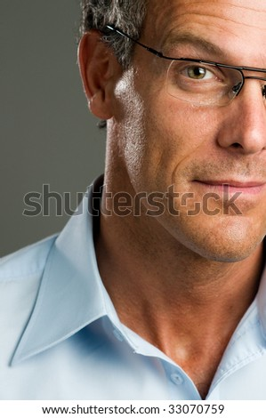 Portrait of half mature man looking at camera with a pair of glasses. - stock photo