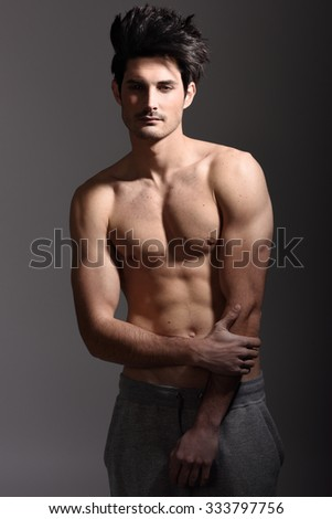 Portrait of half naked sexy body of muscular athletic man. Studio shot