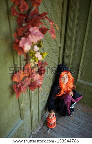 Portrait of Halloween girl with red hair sitting on the porch of dilapidated house - stock photo