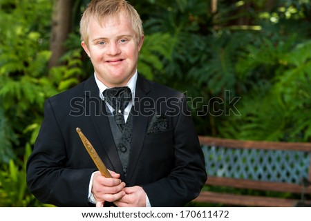 Portrait of handicapped drummer boy in black suit outdoors. - stock photo