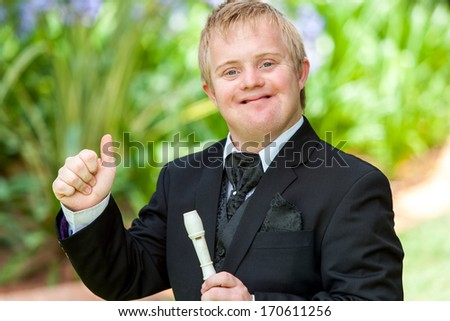 Portrait of handicapped musician in black suit doing thumbs up outdoors. - stock photo