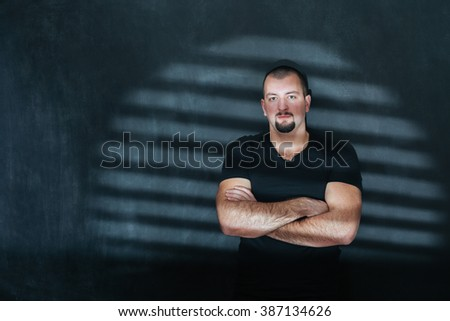Portrait of handsom man standing by the window with shadows from blinds on - dark tone,mood