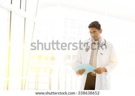 Portrait of handsome Asian Indian medical doctor walking and reading on medical report, outside hospital building block, beautiful golden sunlight at background. - stock photo