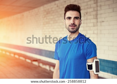 portrait of handsome athlete with stubble, earphones and armband (intentional sun glare) - stock photo