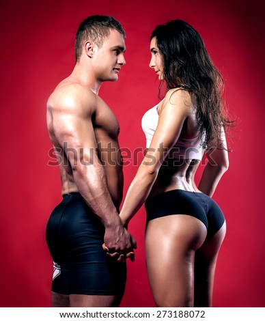 Portrait of handsome athletic couple over red background. Man and woman looking at each other. - stock photo