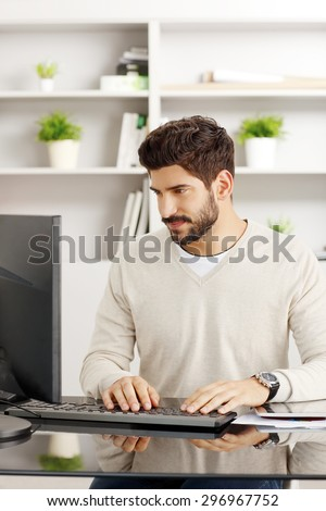 Portrait of handsome bearded graphic designer at workplace. Young creative man sitting in front of computer and checking emails at office. Small business.  - stock photo