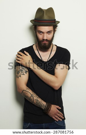 Portrait of handsome bearded man in hat.Brutal boy with tattoo