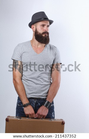 Portrait of handsome bearded man in hat standing with bad, isol