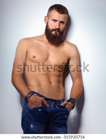 Portrait of handsome bearded man standing, isolated on grey background - stock photo