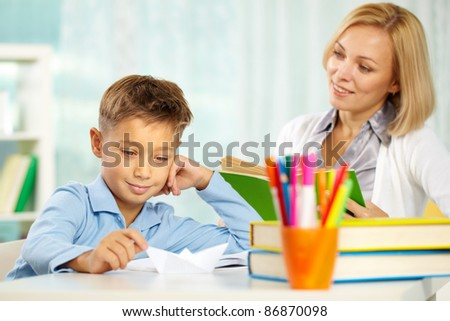Portrait of handsome boy at workplace with his tutor sitting near by and looking at him - stock photo