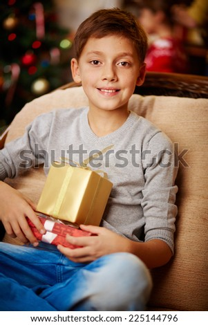 Portrait of handsome boy with giftboxes looking at camera - stock photo