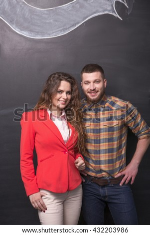 Portrait of handsome businessman and beautiful businesswoman posing over black background in studio. Happy people smiling and looking at camera. - stock photo