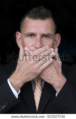 portrait of handsome businessman covering mouth with his hands - stock photo