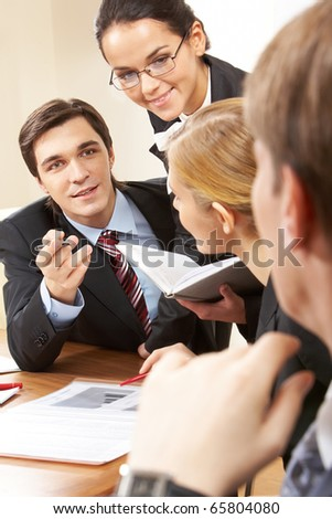 Portrait of handsome businessman explaining something to his colleagues with smart woman near by - stock photo