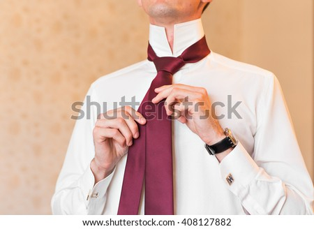 Portrait of  handsome businessman in suit putting on necktie indoors close-up - stock photo