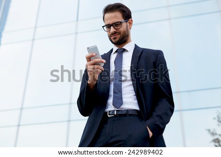 Portrait of handsome businessman looking at cell phone standing near office - stock photo