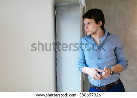 Portrait of handsome businessman looking out of window - stock photo