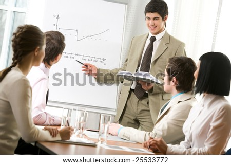 Portrait of handsome businessman pointing at graph on board and looking at his co-workers with smile - stock photo