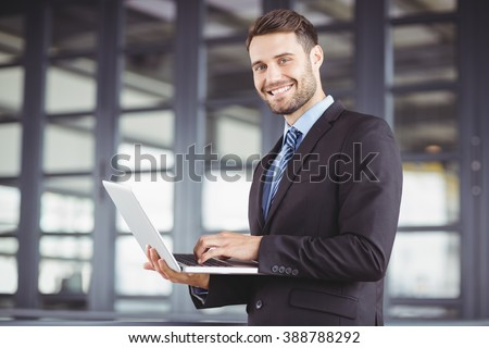Portrait of handsome businessman smiling while using laptop in office - stock photo