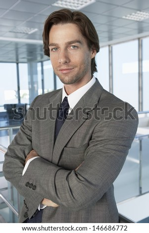 Portrait of handsome businessman standing arms crossed in office