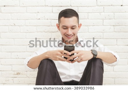 portrait of handsome businessman texting on mobilephone while sitting casually - stock photo