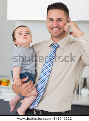 Portrait of handsome businessman using cellphone while carrying baby boy in house - stock photo