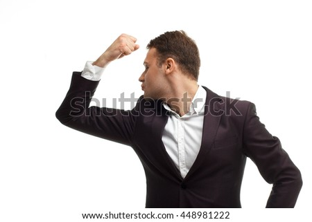 Portrait of handsome businessman wearing black suit shows biceps isolated on white