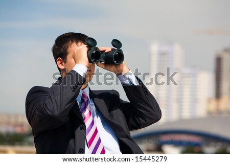 Portrait of handsome businessman with binoculars in hands looking through it in the downtown - stock photo