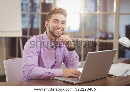 Portrait of handsome businessman with hand on chin working on laptop in creative office - stock photo