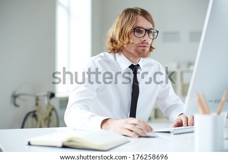 Portrait of handsome businessman working with computer in office - stock photo