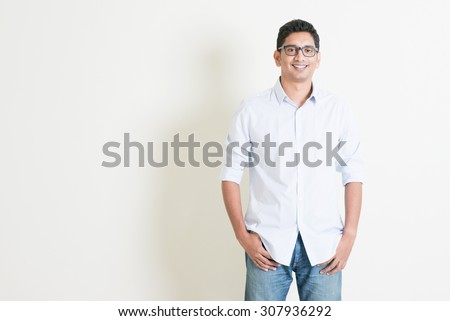 Portrait of handsome casual business Indian male smiling, hands in pocket, standing on plain background with shadow, copy space at side. - stock photo